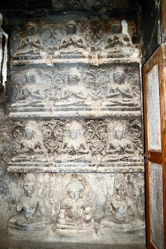 Ein Relief mit 12 Buddhas an der Wand eines Schreins