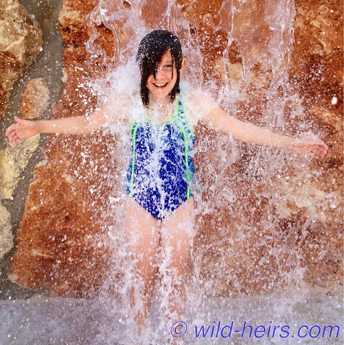 McKinley enjoys the waterfall feature at Quarry Splash Pad in Leander, TX