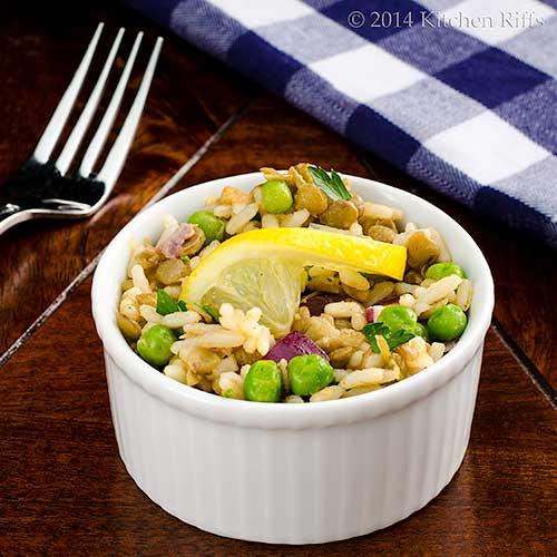 Lentil, Rice, and Pea Salad with lemon slice garnish in ramekin, fork and napkin in background
