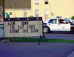 slow down cop hides behind sign