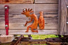 Rusted Kokopelli figure hanging on old buckboard #kokopelli #buckboard  #antiquebuckboard #oldbuckboard