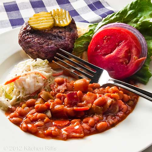 Baked Beans with Bacon on Plate with Grilled Hamburger and Cole Slaw