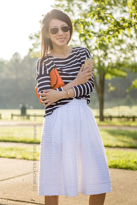 navy striped top with pom poms, orange clutch, white midi skirt