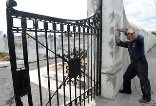 A Navy Diver drills a hole into a column where a brass dedication plaque will be secured next to the Commodore Oliver Perry cemetery gate at Lapeyrouse Cemetery.
