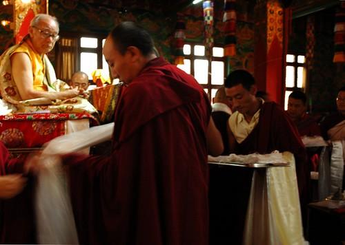 A Tibetan lama prepares a khata during a mandala offer to His Holiness Jigdal Dagchen Sakya, wearing traditional silk garments on his throne, Sakya Lamdre, Tharlam Monastery of Tibetan Buddhism, Boudhanath, Kathmandu, Nepal by Wonderlane