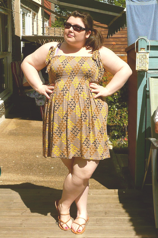 Image: Me (short, fat, brunette, pale caucasian skin) stands in a garden with hands on hips in a brown sundress with small hearts, brown sandals and sunglasses, and hair in a side ponytail.