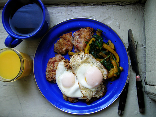 fried eggs on potato bean cakes, spinach, and peppers with coffee and OJ
