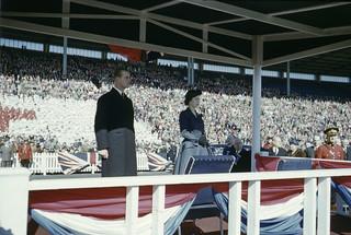 Princess Elizabeth and Prince Philip on stage in front of large audience / La princesse Élisabeth sur une estrade avec prince Philip devant une foule