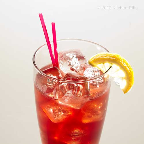 Sloe Gin Fizz with Lemon Garnish, White Background