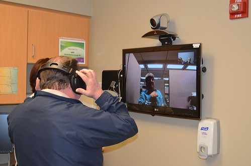 USDA Rural Utilities Service General Field Representative Wayne Ahlgren  tests the telemedicine equipment on a recent tour of Avera Health in Sioux Falls, South Dakota with Loren Eitreim, Video Technician at Avera shown on the monitor.