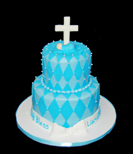 2 tier Christening Cake with a sleeping baby under a cross