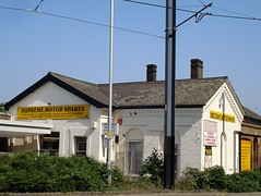 "A white-painted building with pointed gables and a grey roof. Signs on the building read ""Supreme Motor Spares"" and ""Discount Motor Spares"". Overhead tram power lines are visible at the top of the photo.  Some greenery has been planted in front of the building."