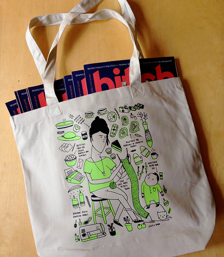 Image shows a cream colored tote bag with a green and black illustration of a woman with a beehive hairdo knitting a scarf sitting on a stool next to a toddler who is standing on top of a cat. They are surrounded by illustrations of pie, candles, hats, flowers, a sewing machine, mittens, among other tiny images. The tote bag is lying on a wood table with several issues of Bitch magazine popping out of the top.