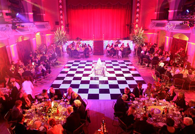 Customers sitting at round dining tables on a black and white chequered dance floor in Winter Gardens