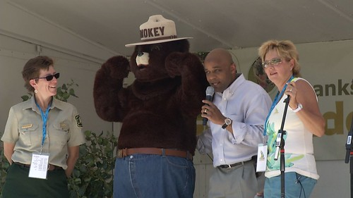 (From Left to Right) National Get Outdoors Day Colorado Coordinator Susan Alden-Weingardt, Smokey Bear, Mayor Michael Hancock, and Emcee, Coach Stacy Fowler celebrate National Get Outdoors Day Colorado 2012 on the main stage of the event.