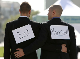 two grooms wearing just married signs on their backs