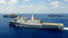In this file photo, the amphibious transport dock ship USS New Orleans (LPD 18), foreground, and the amphibious dock landing ship USS Pearl Harbor (LSD 52), top, transit the Indian Ocean May 8 with the amphibious assault ship USS Makin Island (LHD 8). (U.S. Navy photo by Chief Mass Communication Specialist John Lill)
