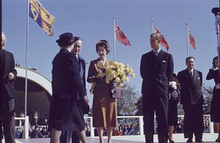 Princess Elizabeth and Prince Philip holding flowers on stage with several men and women / La princesse Élisabeth tenant des fleurs sur une estrade avec plusieurs hommes et femmes
