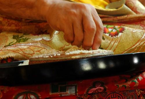 Closeup of the hand of His Holiness Jigdal Dagchen Sakya making a rice visualized mandala offering, mandala plate, rice tray, silks, ritual tradition, Sakya Lamdre, Tharlam Monastery of Tibetan Buddhism, Boudhanath, Kathmandu, Nepal by Wonderlane