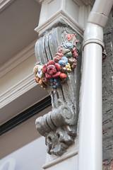 <p>Huize de Moriaan, detailfoto van een sculptuur van een bloementros aan de gevel op straatniveau. Foto: Anna van Kooij.</p>
