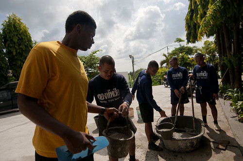 Fireman Apprentice Colby Jackson-King receives a bucket of wet cement from a member of the Royal Thai Navy.