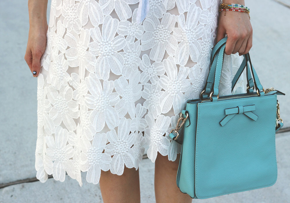 Blue bow bag and white floral lace overlay midi skirt