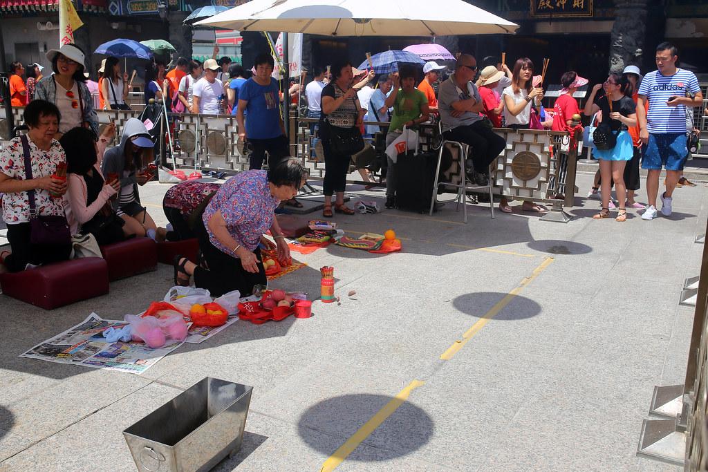 黃大仙廟 Hong Kong / Sigma 35mm / Canon 6D 本來想說早點出門去黃大仙廟拜拜,但一到,我傻眼!這裡變成中國旅客觀光點之一,一車一車的人湧入!有點不是很舒服這種擁擠的狀況。  但我還是觀察一下關於求籤、擲杯和台灣有沒有什麼不同,唯一不同的就是黃大仙廟沒有供桌,所以大家只好找一個地方放自己的供品,然後在陽傘底下努力搖出可能的掛籤。  我自己還是在人群中向黃大仙問了一些事情,希望可以給我點 sign 讓我知道我改怎麼辦才好,雖然這個問題我問了快一年了。  Canon 6D Sigma 35mm F1.4 DG HSM Art IMG_1463 Photo by Toomore