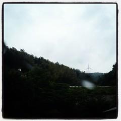 バスで山を登っています。山の上には風車が何基か。