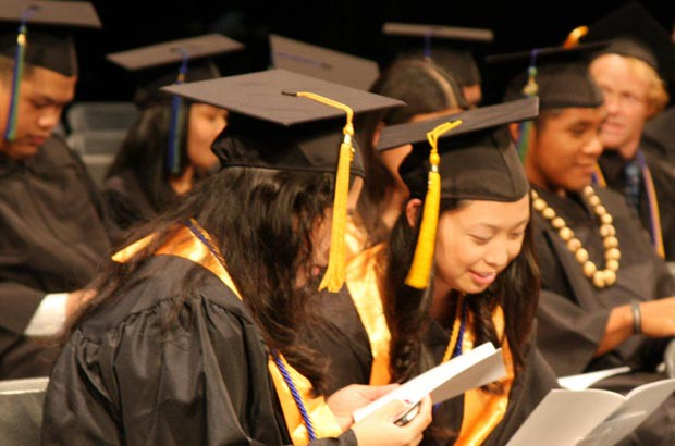 <p>Anxious and eager Maui College graduates examine the commencement program, waiting for their names to be called</p>