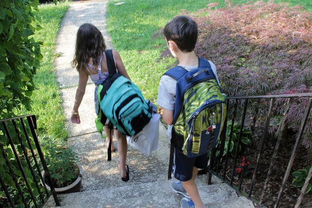 the kids, with their heavy backpacks, head out to the bus