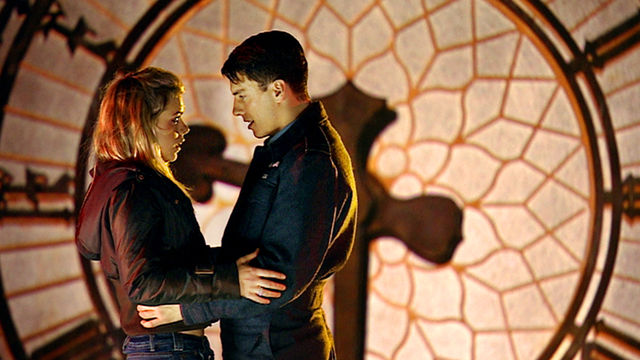 A man and woman stand in front of a huge clock. The face each other, and their hands are on each other's hips. The woman is blonde and wears a hooded jacket and blue jeans. The man has dark hair and wears a dark, military-style suit.