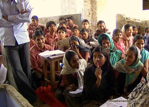 Schoolchildren in Abhaneri sit cross-legged in an open-air classroom, often sharing space with several other classes