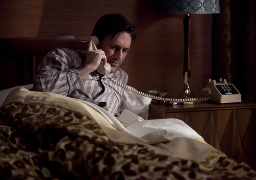 Don picking up the phone in bed wearing pajamas