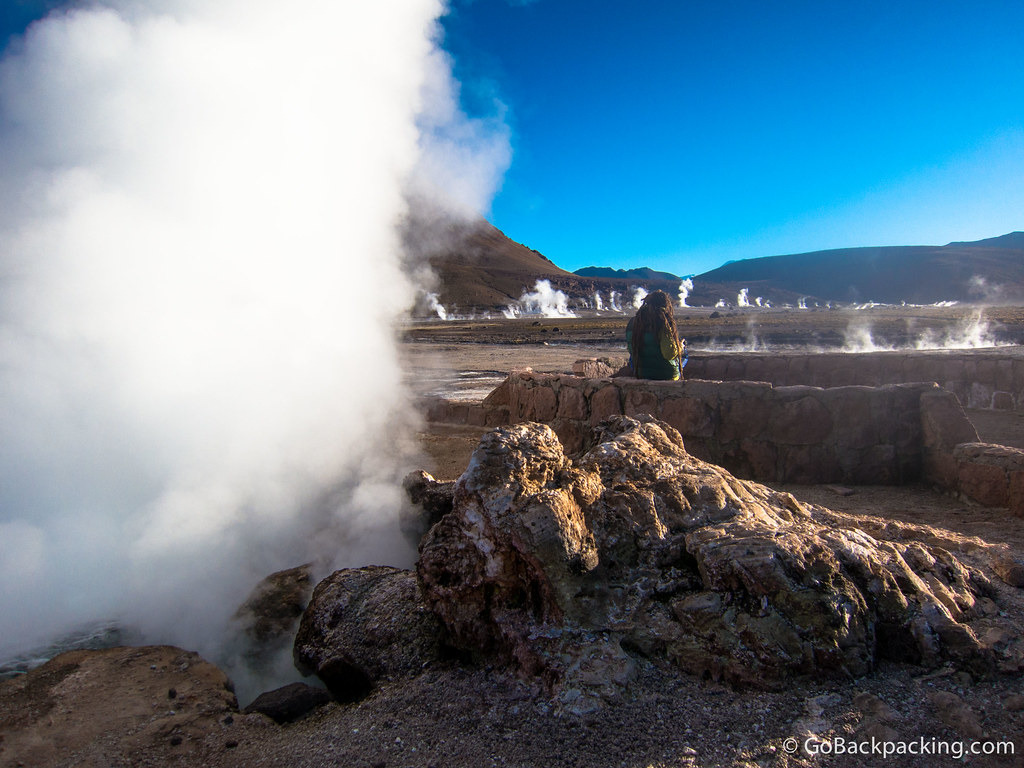 A dreadlocked visitor takes a break next to one of the largest geysers