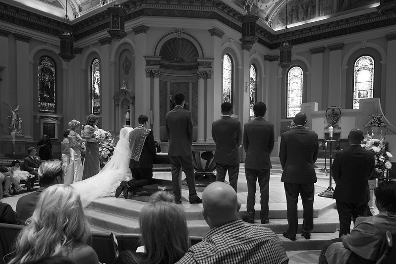 Wedding Couple Kneel Before Altar