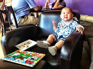 A baby with something to say sitting in a chair with a croissant and a puzzle