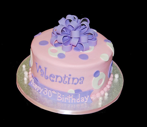 pink and purple sassy circles cake topped with a purple bow for a 30th birthday