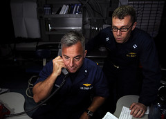 PACIFIC OCEAN (May 11, 2012) Cmdr. Mark Morin, chief of the incident management branch of the United States Coast Guard, stands watch as Lt. Karl Hjembo, assigned to Destroyer Squadron 1 observes as part of the Oceania Maritime Security Initiative (OMSI) in the sea combat module aboard the aircraft carrier USS Carl Vinson (CVN 70). (U.S. Navy photo by Mass Communication Specialist 3rd Class Nicolas C. Lopez)