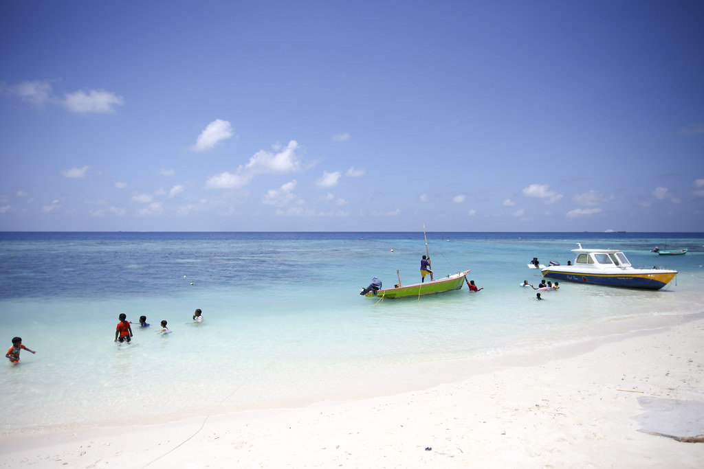 Maldives kids playing in the sea, on Maafushi island