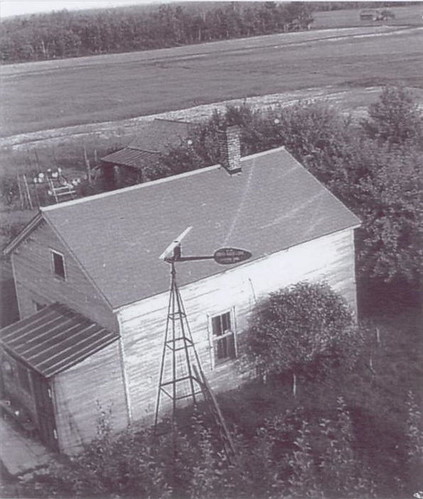 Farmhouse with landing strip in the field behind it, 1940s.