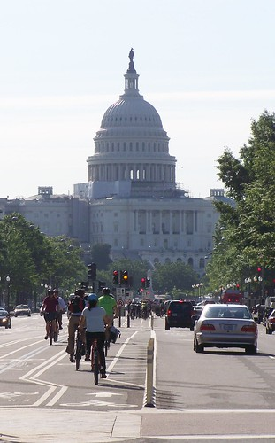 Bicyclists in the cycletrack on Pennsyvlania Avenue NW, Washington, DC, with the US Capitol in the foreground (cropped)