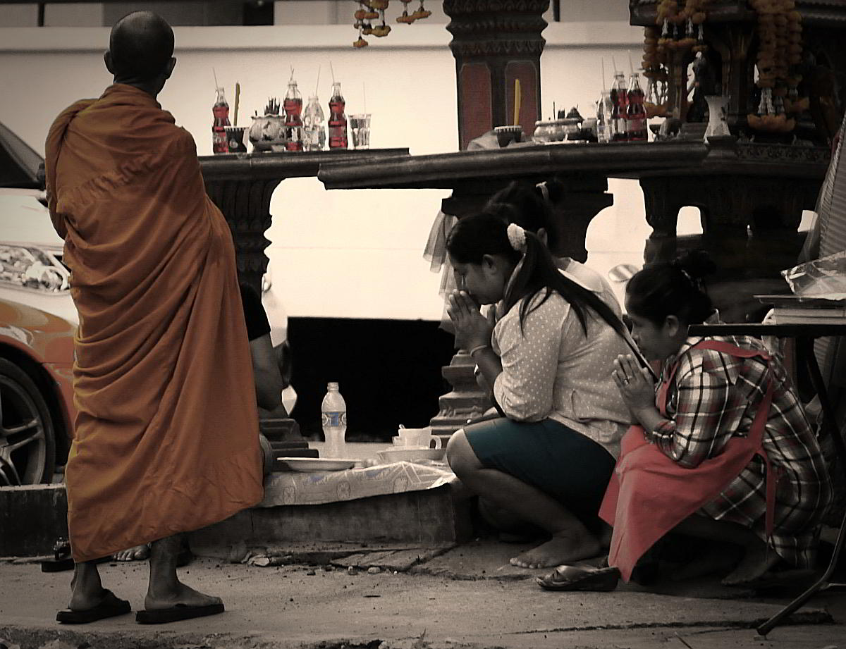 Thai women respectfully wai a monk in Pattaya Thailand