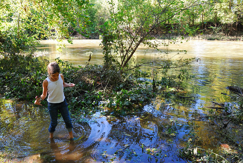 Picture of girl wading through a flooded Sac River Trail along the Little Sac River