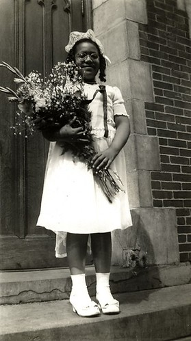 a black and white photo of Audre Lorde in the early 1940s, as a Roman Catholic schoolgirl, dressed for her First Communion.