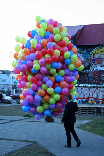 Man walks cat in basket under balloons, Reykjavik