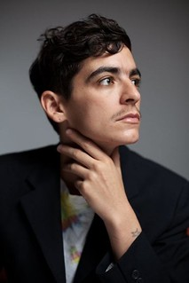 Portrait of JD Samson in front of a grey background. JD Samson is wearing a black blazer and gazing into the distance with her hand placed on her neck.