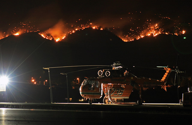 Guaje Ridge burns behind a skycrane at Los Alamos Airport on July 5th, 2011.  Photo by Ethan Frogget.