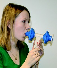 Student blowing into spirometer