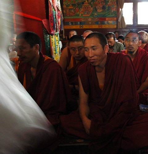 Senior monks, Tibetan lamas, chat with inner bemusement, while white kataks are distributed, traditional robes, silk decorations, wall murals depicting the life events of Lord Buddha, Sakya Lamdre, Tharlam Monastery, Boudha, Kathmandu, Nepal by Wonderlane