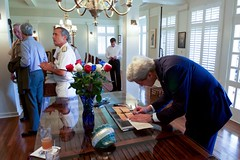 U.S. Secretary of State John Kerry signs the guest book at the quarters of U.S. Navy Admiral Harry Harris, Commander of Pacific Command, after arriving at Joint Base Pearl Harbor-Hickam, Hawaii, on May 25, 2016, for a military briefing from Pacific Theater Combatant Commanders amid his travels back to Washington, D.C., from joining President Obama's trip to Vietnam. [State Department photo/ Public Domain]